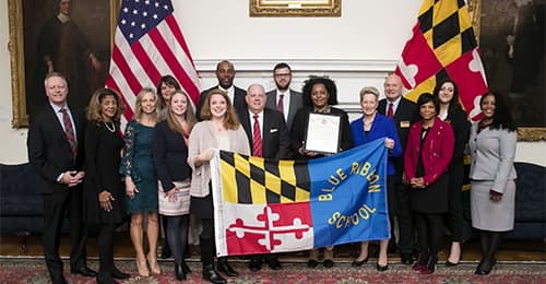 Representatives from MSDE, HCPSS, MVMS, and Annapolis hold a Blue Ribbon Banner.