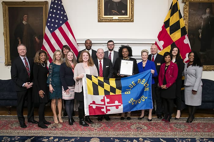 "Representatives from HCPSS, Mount View Middle School, MSDE, and the Governor hold a ""Blue Ribbon School"" banner."