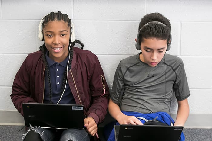 A female and a male students wearing headphones and looking at laptops.