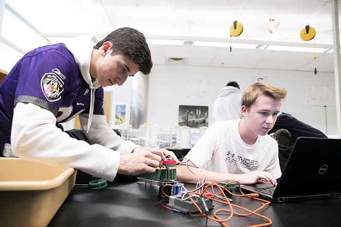 Two male students working on computer assembly and programming.