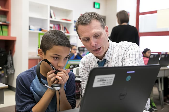 David Floyd looking at a computer with a male student.