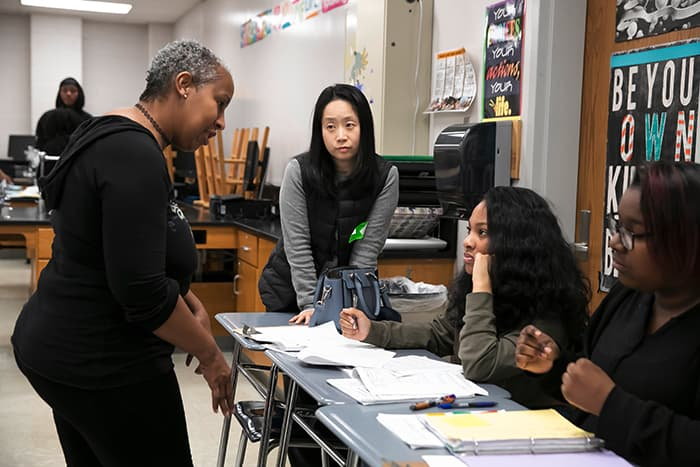 Female HCPSS teacher speaks to students while female South Korean teacher listens.