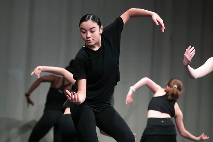 A group of female dancers moving their arms.