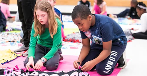 A male and female student make a quilt together.