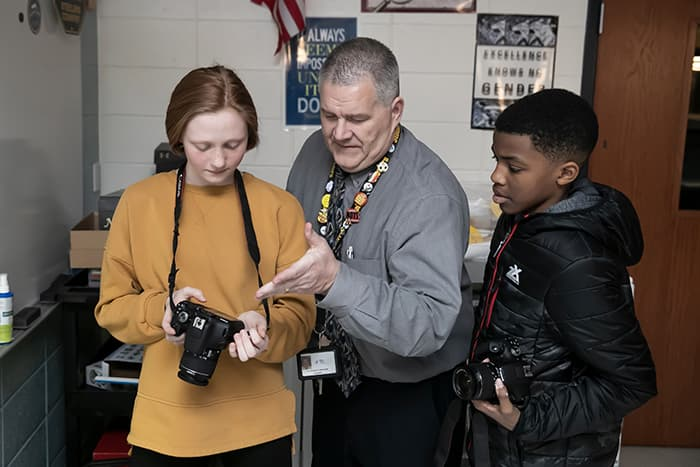 Doug Spicher teaches a male and female student how to use a camera.