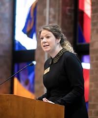 Liz Crammond speaking at a podium.