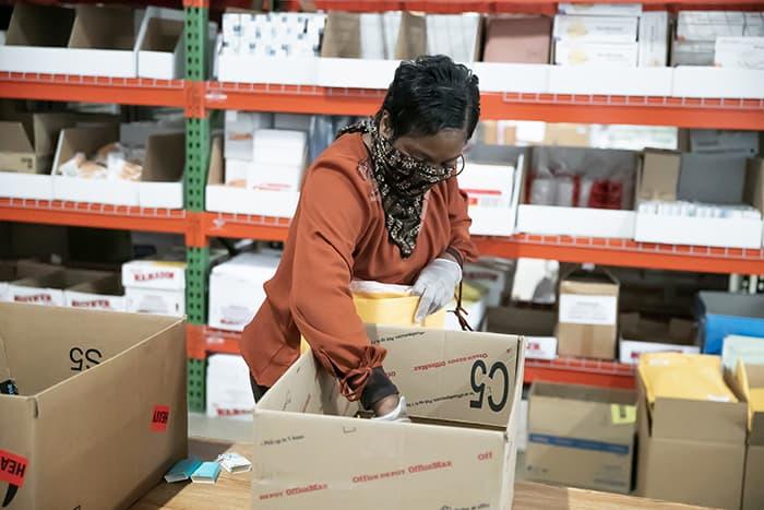 A woman assembles supply packs.
