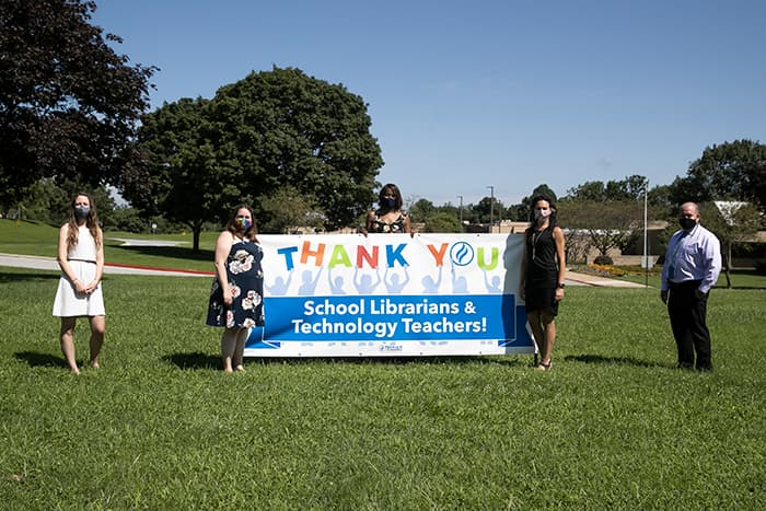 Teachers standing with a thank you school librarians and technology teachers sign.
