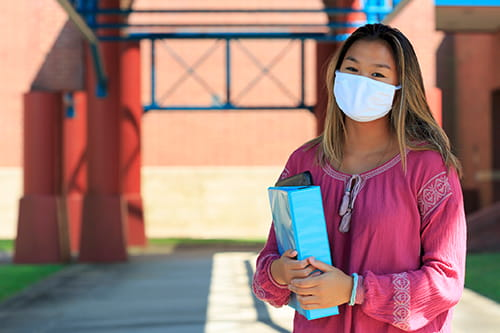 Female student standing in fron of her school building wearing a facemask.