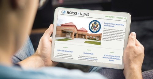 man on iPad looking at HCPSS news site
