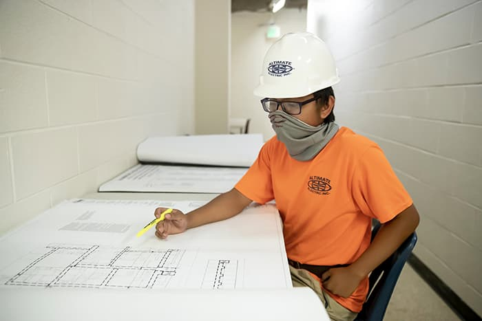 Christopher Borja looks at a blueprint.