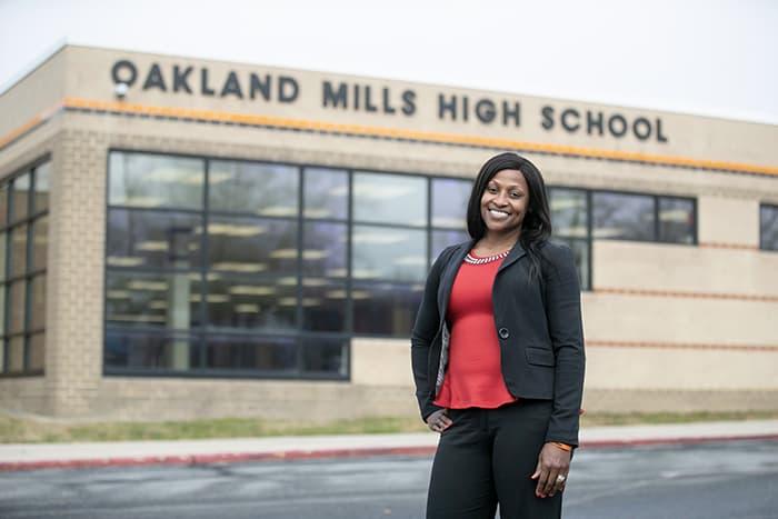 Raymona Reid standing outside of Oakland Mills High School.