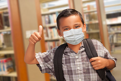 boy wearing protective face mask in school and giving a thumbs up