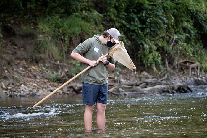 Male student examining a net while standing in stream.