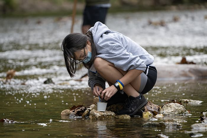 Female student standing in a stream taking a water sample.