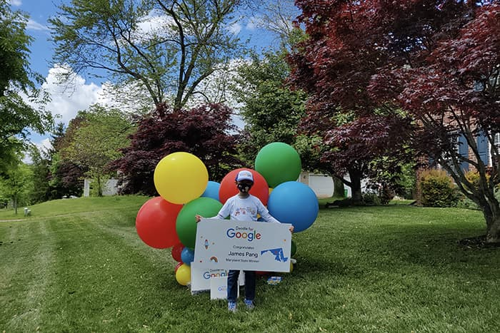 James Pang holding a sign and surrounded by balloons.