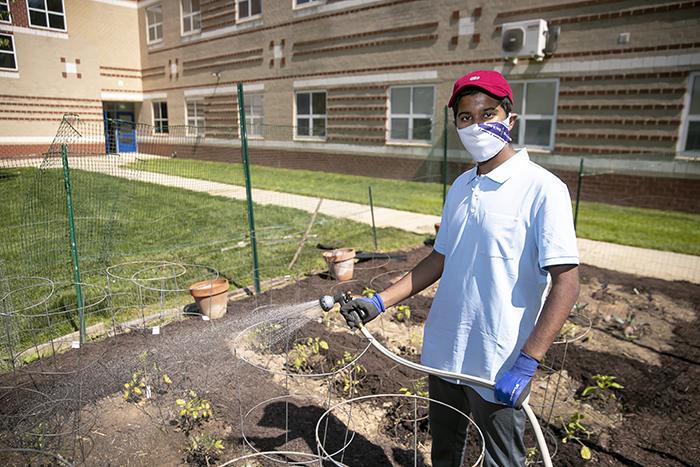Ishaan Busireddy watering a garden.