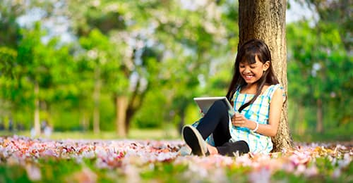 A young girl reading under a tree.