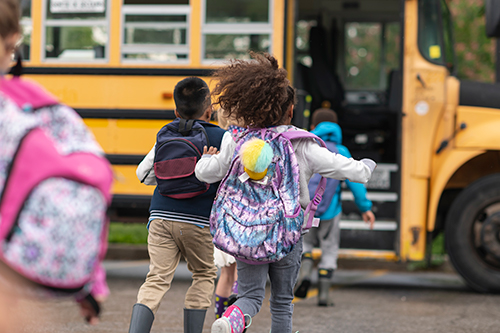 Kids running to get on bus.