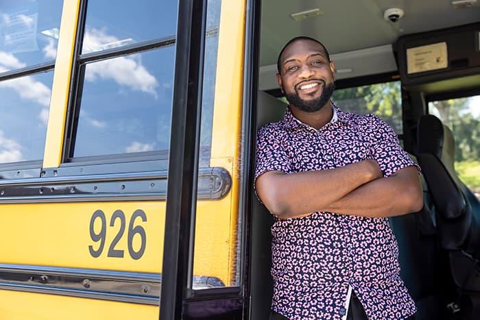 Javion Hinmon stands inside a school bus.
