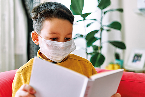 A young boy wearing a face mask and reading a book at home.