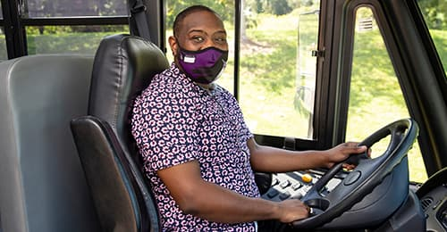 Javion Himon sits in the driver's seat of a school bus.